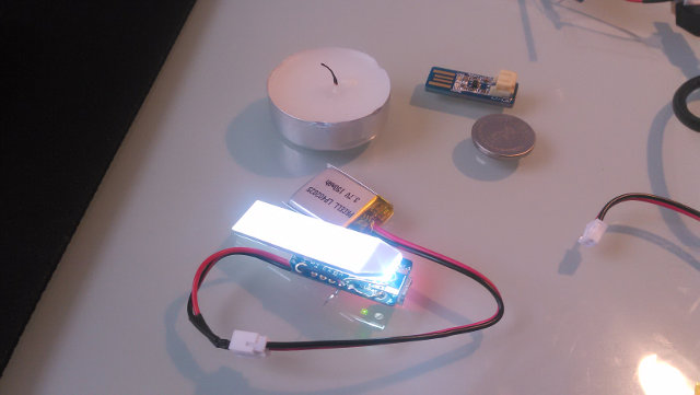 Adafruit Trinket with a backlight module attached, alongside a tealight